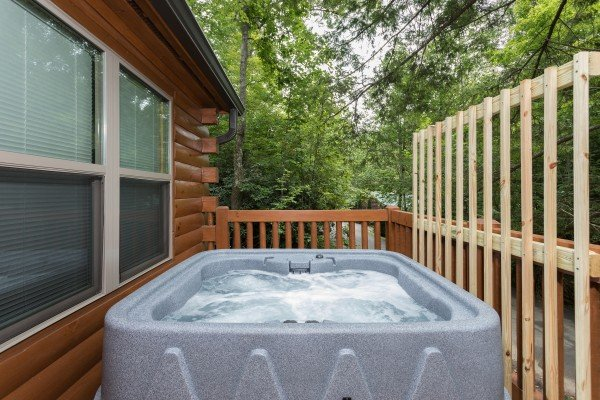 Hot tub and privacy lattice at Paws on the Porch, a 2 bedroom cabin rental located in Gatlinburg