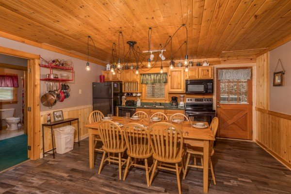 Dining for eight and kitchen with black appliances at Timber Creek, a 4 bedroom cabin rental located in Pigeon Forge