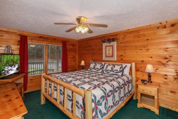 Bedroom with a log bed and TV at Timber Creek, a 4 bedroom cabin rental located in Pigeon Forge
