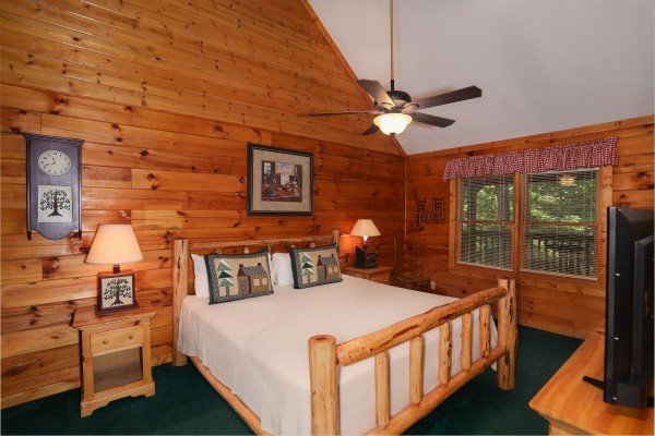 King bedroom with nightstands and a TV at Timber Creek, a 4 bedroom cabin rental located in Pigeon Forge