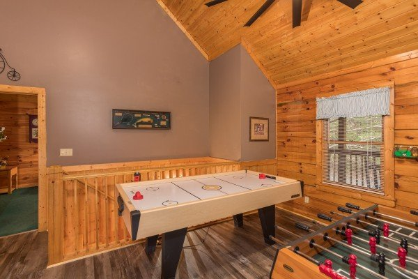 Air hockey and foosball tables in the game loft at Timber Creek, a 4 bedroom cabin rental located in Pigeon Forge