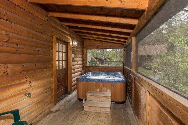Hot tub on a screened porch at Timber Creek, a 4 bedroom cabin rental located in Pigeon Forge