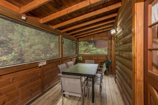 Screened deck with dining space for six at Timber Creek, a 4 bedroom cabin rental located in Pigeon Forge