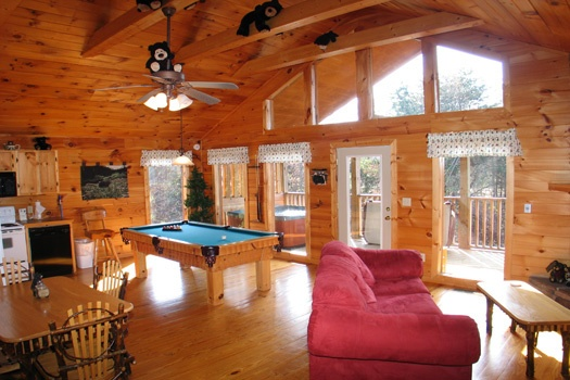 open layout of living room with pool table and sofa bed at bear heaven a 1 bedroom cabin rental located in pigeon forge