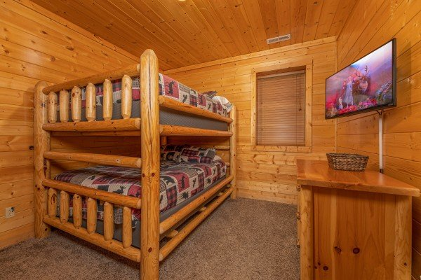 Bunk beds, dresser, and TV in a bedroom at Grizzly's Den, a 5 bedroom cabin rental located in Gatlinburg