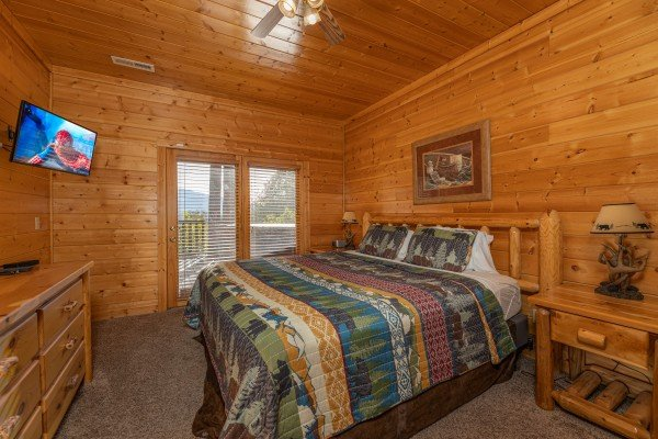 Bedroom with a dresser, TV, and deck access at Grizzly's Den, a 5 bedroom cabin rental located in Gatlinburg