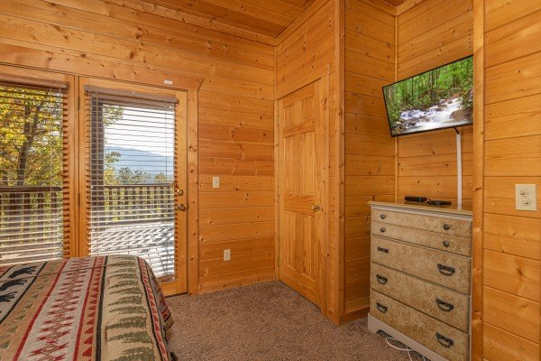 Dresser, TV, and deck access in a bedroom at Grizzly's Den, a 5 bedroom cabin rental located in Gatlinburg