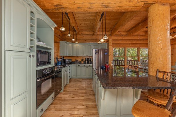 Kitchen with green cabinets and black appliances at Grizzly's Den, a 5 bedroom cabin rental located in Gatlinburg