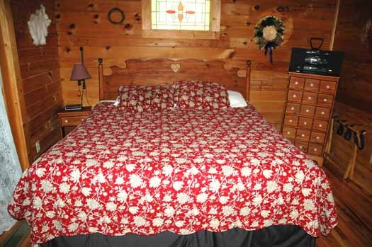 bedroom with king sized bed and ensuite at bear kisses & hugs a 1 bedroom cabin rental located in pigeon forge