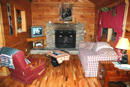 living room with stone fireplace and sofa bed at bear kisses & hugs a 1 bedroom cabin rental located in pigeon forge