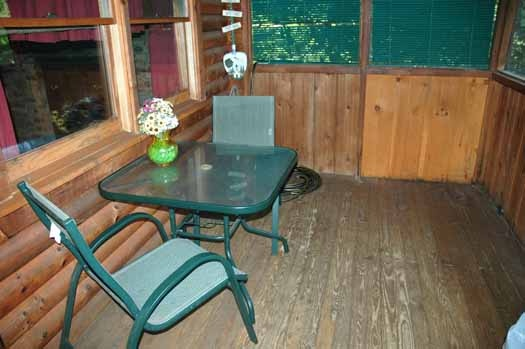 patio furniture table and chairs on screened deck at bear kisses & hugs a 1 bedroom cabin rental located in pigeon forge