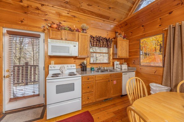 Kitchen with white appliances at Fallin' in Love, a 1 bedroom cabin rental located in Gatlinburg