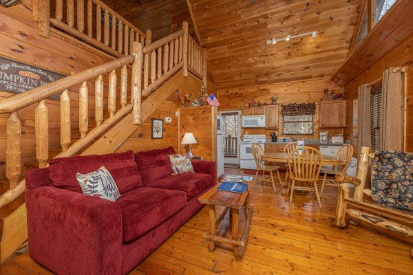Sofa and chair in a living room at Fallin' in Love, a 1 bedroom cabin rental located in Gatlinburg