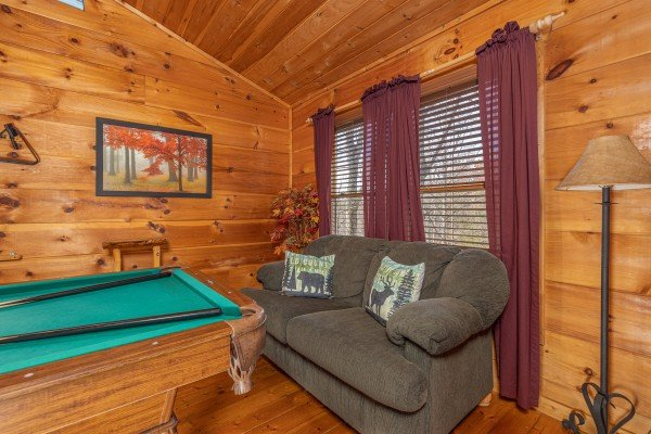 Sofa and pool table in the loft at Fallin' in Love, a 1 bedroom cabin rental located in Gatlinburg