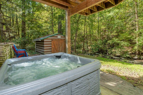 Hot tub on a covered patio at Stream On! A 2 bedroom cabin rental located in Pigeon Forge