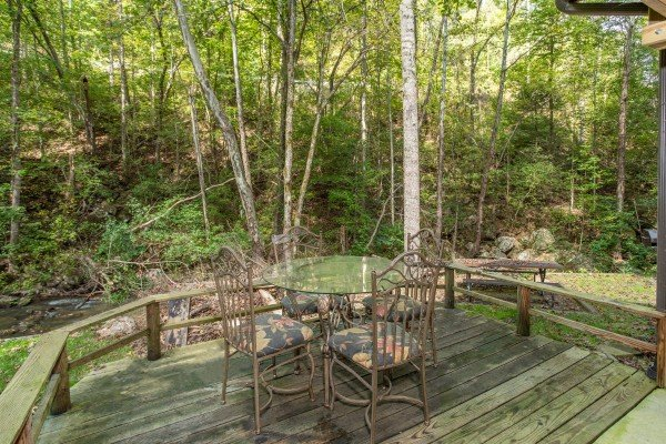 Dining space for four on a lower deck at Stream On! A 2 bedroom cabin rental located in Pigeon Forge