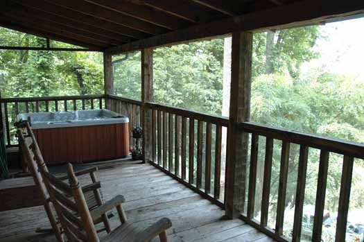 covered deck with hot tub and rockers at smoky mountain romance a 1 bedroom cabin rental located in pigeon forge