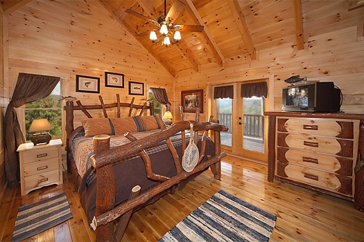 third floor bedroom with king sized bed and tv on top of dresser at lookout lodge a 4 bedroom cabin rental located in pigeon forge