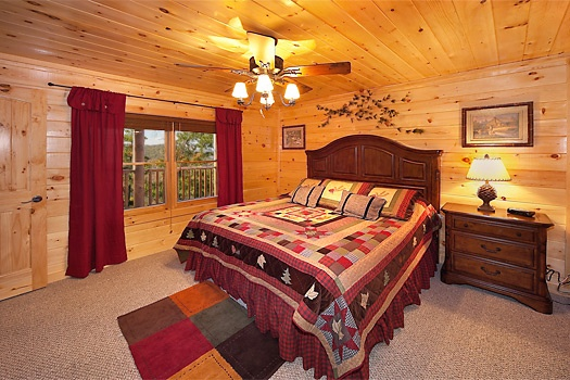 king bed in first floor bedroom at lookout lodge a 4 bedroom cabin rental located in pigeon forge