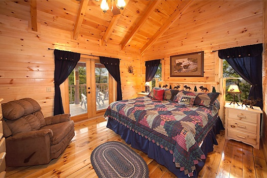 third floor bedroom with king sized bed at lookout lodge a 4 bedroom cabin rental located in pigeon forge