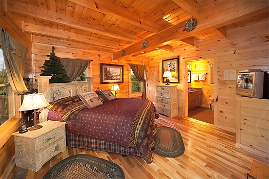 queen bed in main level bedroom with ensuite at lookout lodge a 4 bedroom cabin rental located in pigeon forge