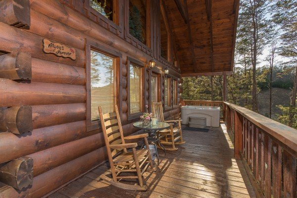 rocking chairs and hot tub on a covered deck at always & forever a 1 bedroom cabin rental located in pigeon forge