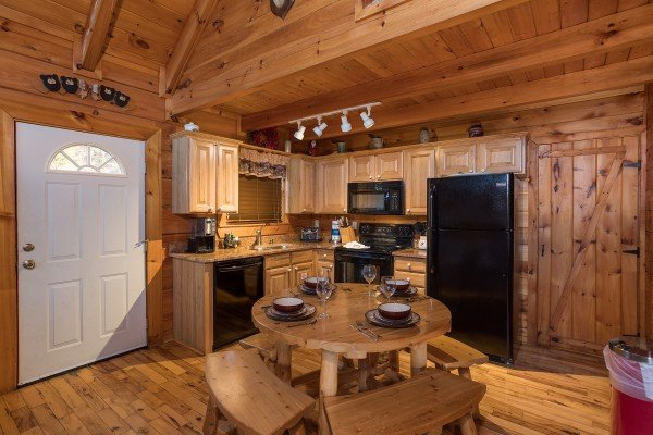 dining table with bench seating for four at always & forever a 1 bedroom cabin rental located in pigeon forge