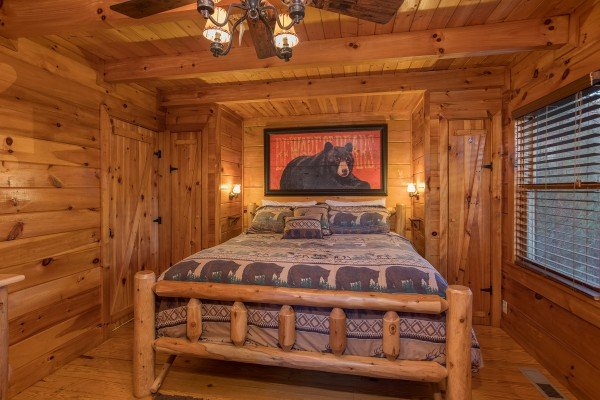 king sized log bed in the master bedroom at always & forever a 1 bedroom cabin rental located in pigeon forge