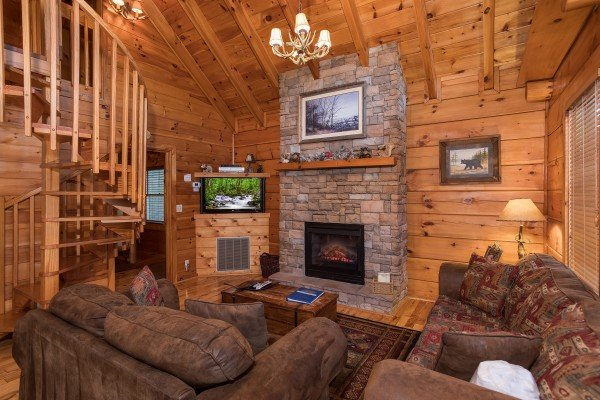 living room with a stone fireplace and spiral staircase at always & forever a 1 bedroom cabin rental located in pigeon forge