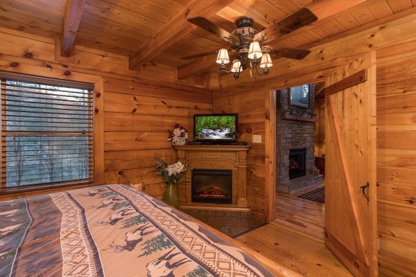 master bedroom with fireplace and television at always & forever a 1 bedroom cabin rental located in pigeon forge