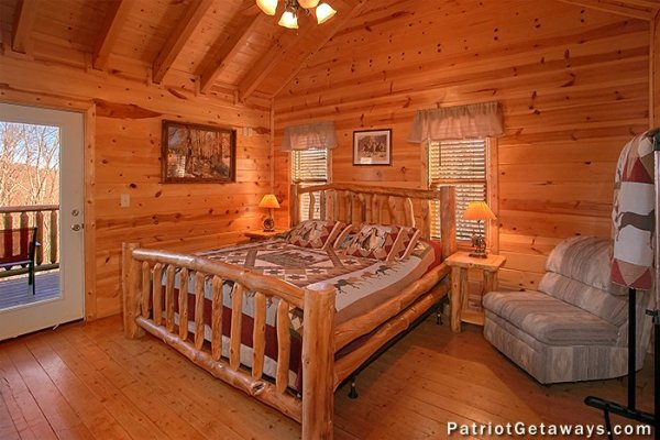 First bedroom with a king log bed and deck access at Tennessee Dreamer, a 5 bedroom cabin rental located in Pigeon Forge