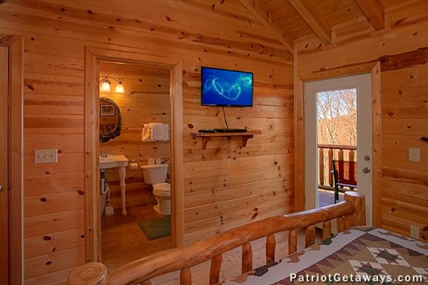 Bedroom with en suite bath, TV, and deck access at Tennessee Dreamer, a 5 bedroom cabin rental located in Pigeon Forge