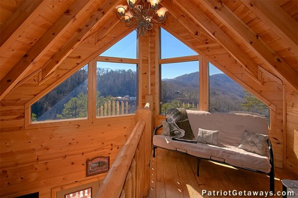 Futon and vaulted windows in the loft space at Tennessee Dreamer, a 5 bedroom cabin rental located in Pigeon Forge
