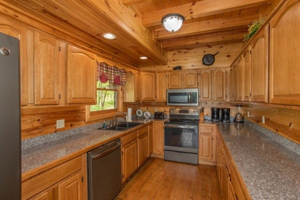 Galley kitchen with stainless appliances at Tennessee Dreamer, a 5 bedroom cabin rental located in Pigeon Forge