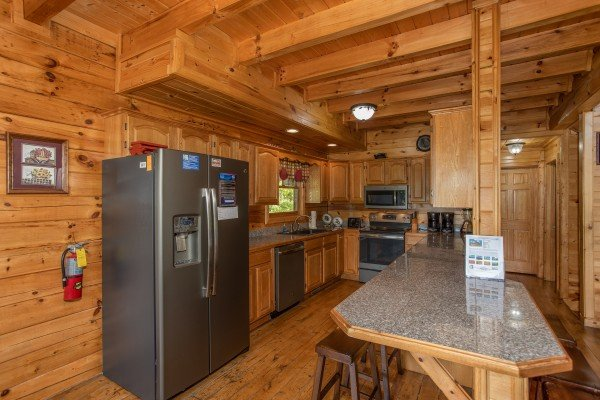 Galley kitchen with stainless appliances & breakfast bar at Tennessee Dreamer, a 5 bedroom cabin rental located in Pigeon Forge