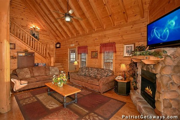 Living room with two sofas, fireplace, and TV at Tennessee Dreamer, a 5 bedroom cabin rental located in Pigeon Forge