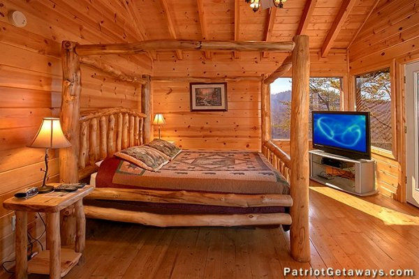 Bedroom with a king log bed and TV at Tennessee Dreamer, a 5 bedroom cabin rental located in Pigeon Forge
