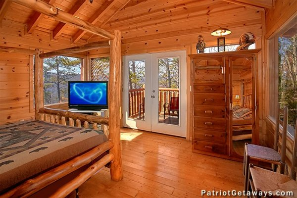 TV, armoire, and deck access in an upstairs bedroom at Tennessee Dreamer, a 5 bedroom cabin rental located in Pigeon Forge