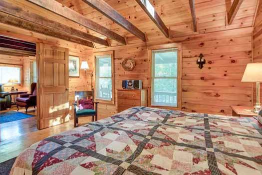 bedroom with beam ceiling at a beautiful river a 1 bedroom cabin rental located in gatlinburg