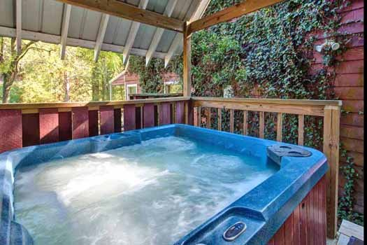 hot tub on a covered deck at a beautiful river a 1 bedroom cabin rental located in gatlinburg