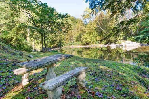 stone picnic table by the river at a beautiful river a 1 bedroom cabin rental located in gatlinburg