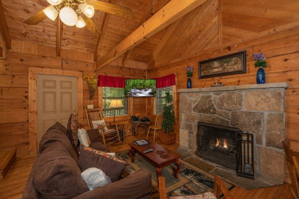 Living room with fireplace, sofa, and vaulted ceiling at Cabin on the Mountain, a 2 bedroom cabin rental located in Gatlinburg