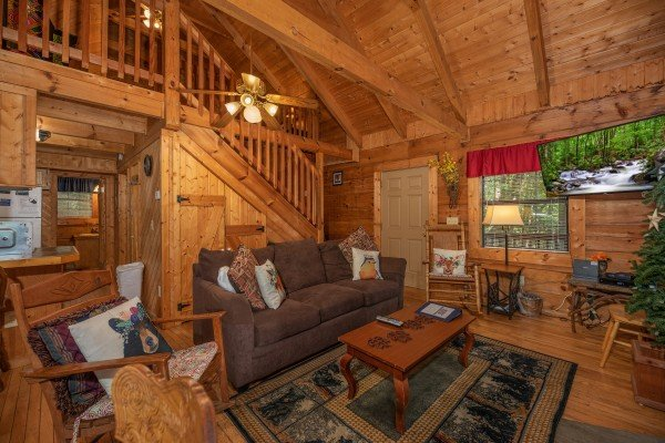 TV, sofa, and chair in a living room at Cabin on the Mountain, a 2 bedroom cabin rental located in Gatlinburg