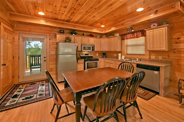 dining space with seating for four and kitchen at an elegant moose a 2 bedroom cabin rental located in pigeon forge