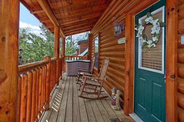 front porch with rockers and hot tub at an elegant moose a 2 bedroom cabin rental located in pigeon forge