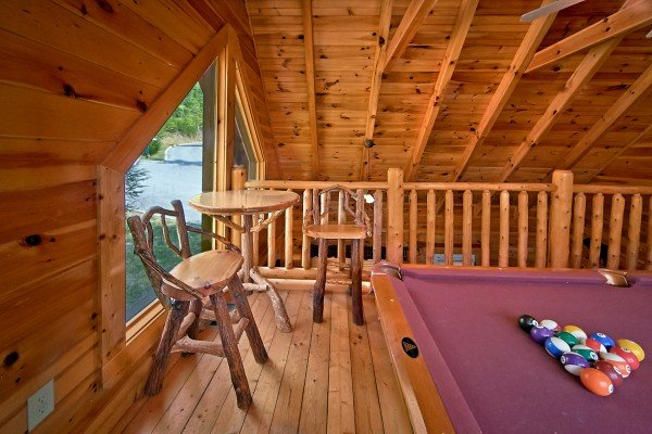 custom log bar table and chairs near the pool table at an elegant moose a 2 bedroom cabin rental located in pigeon forge