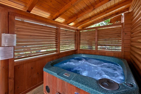 hot tub on a covered deck with privacy fence at an elegant moose a 2 bedroom cabin rental located in pigeon forge