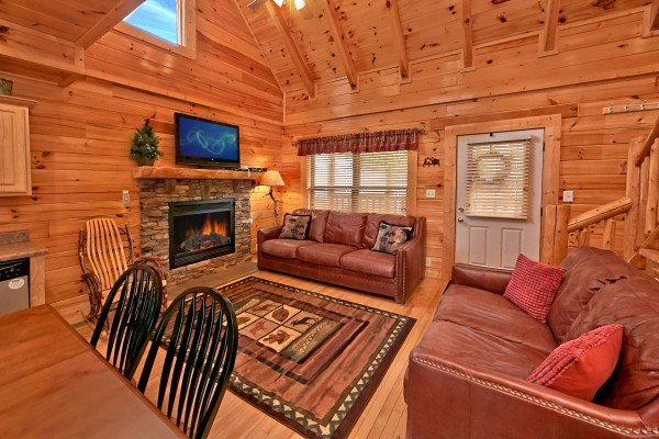 living room with sofa loveseat and stone fireplace at an elegant moose a 2 bedroom cabin rental located in pigeon forge