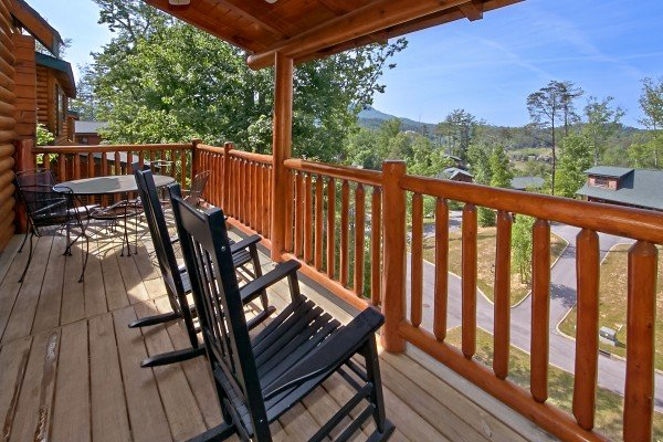 rocking chairs on a covered deck and a mountain view at an elegant moose a 2 bedroom cabin rental located in pigeon forge