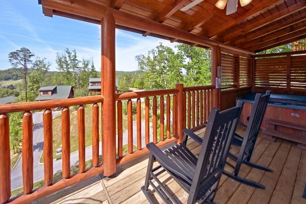 rocking chairs on a covered deck at an elegant moose a 2 bedroom cabin rental located in pigeon forge